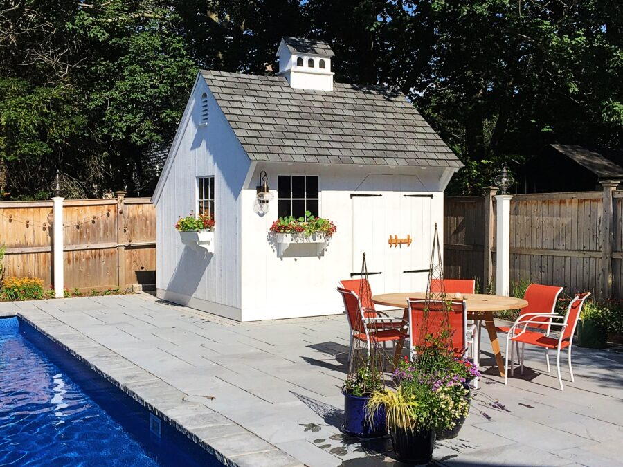 Beautiful, white Saltbox Pool shed with flower boxes and cupola sitting on concrete deck next to pool