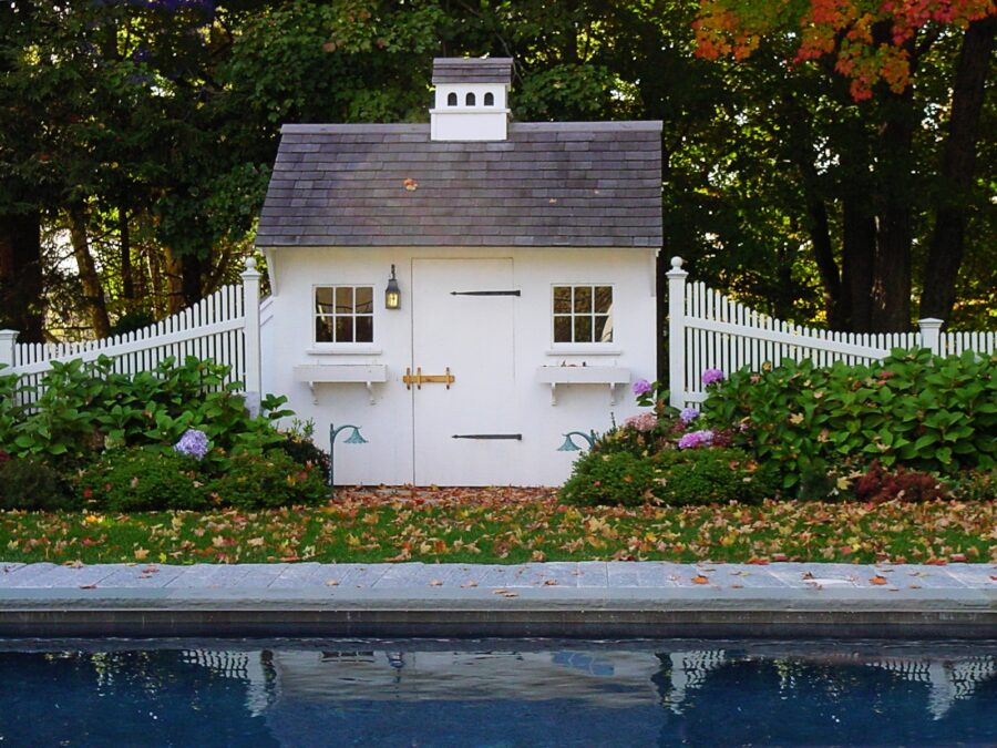 White Pool Shed with beautiful landscaping and fence with view of pool in front