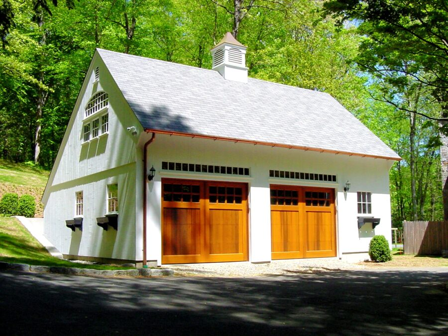 White Saltbox Garage with Stained wood Overhead doors and copper gutters