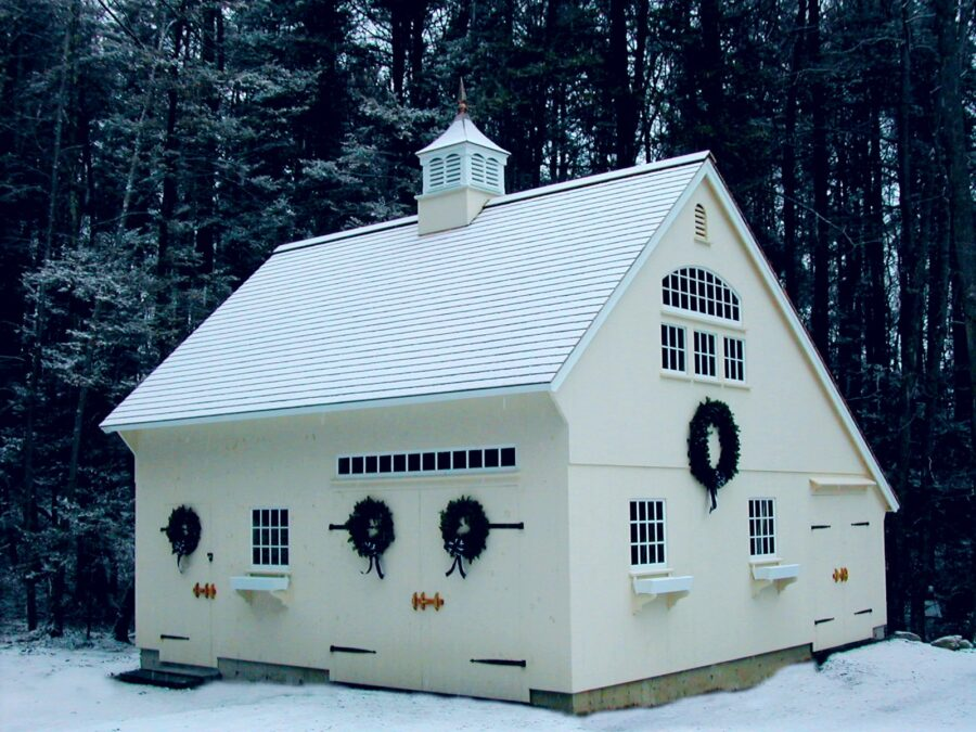 White Saltbox in the snow with wreaths on building