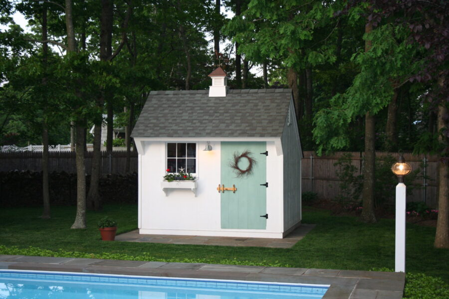 White Pool Shed with green door with lamp post and pool in the background