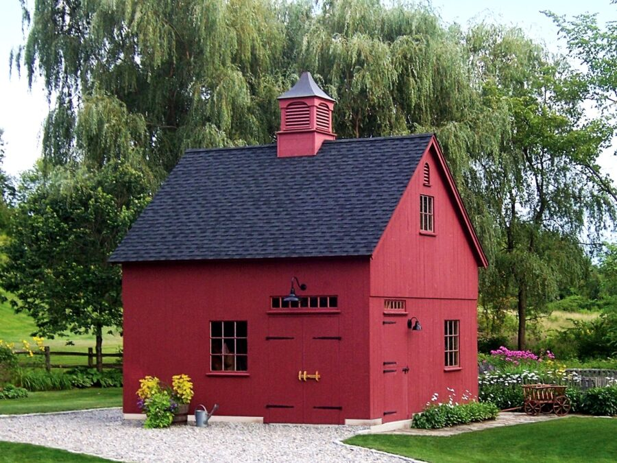 red barn in the spring surrounded by flowers and willow trees