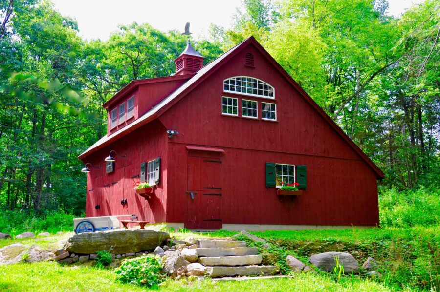 Red 1 1/2 Story Saltbox with wheelbarrow in front and forest in the background