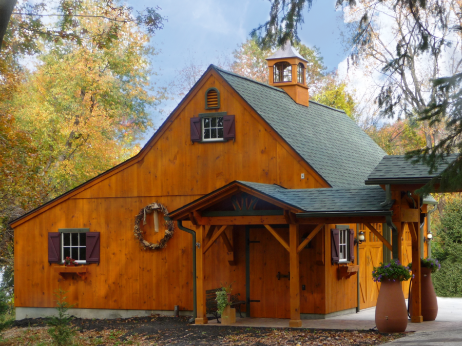 A Naturally stained post and beam barn with awning and trees in the background