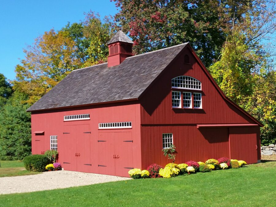 Large Red Barn with doors and windows, a lean-to and flowers all around