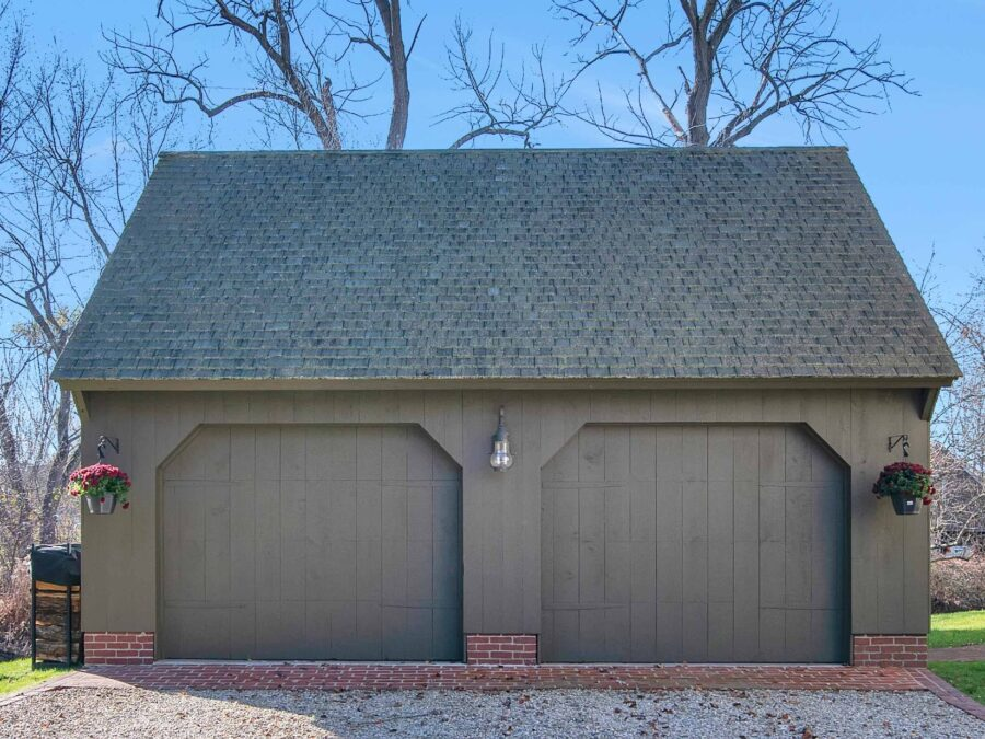 Green Carriage House with brick foundation and blue skies