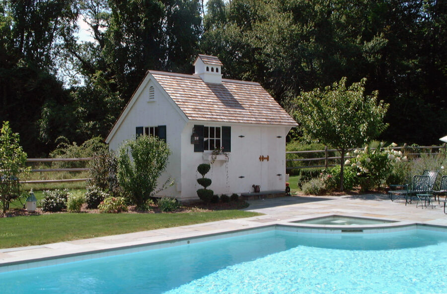 White Saltbox Pool House next to pool with plants and bushes all around