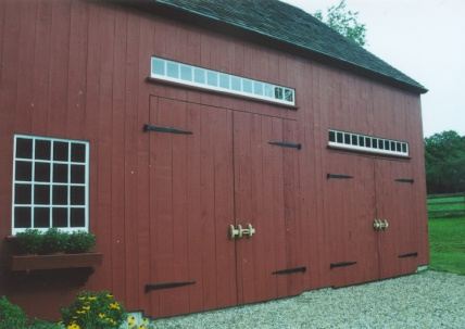 Close-up of red barn doors with transom windows